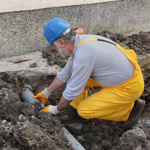 A Plumber Works on Pipe Repair on a Sewer Line.