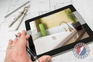 A Contractor's Hand On a Tablet That is Showing a Picture of a Bathroom