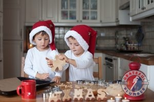 Two Boys in Santa Hats Making Xmas Cookies in Kitchen